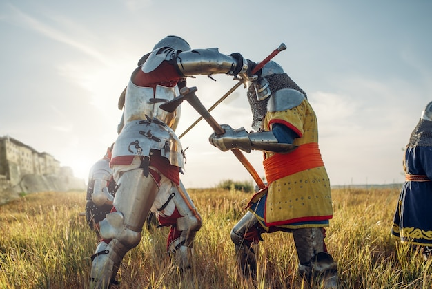 Średniowieczni rycerze w zbrojach i hełmach walczą mieczem i toporem. opancerzony starożytny wojownik w zbroi pozuje w polu