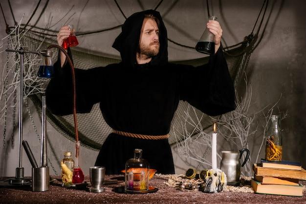 Średniowieczny alchemik, naukowiec, mag patrzy na kolby w swoim laboratorium.