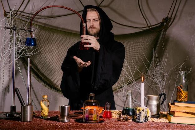 Średniowieczny alchemik, naukowiec, odprawia rytuał w swoim laboratorium.