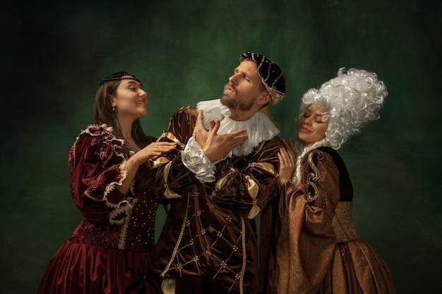 Średniowieczny młody mężczyzna i kobiety w staromodnym stroju