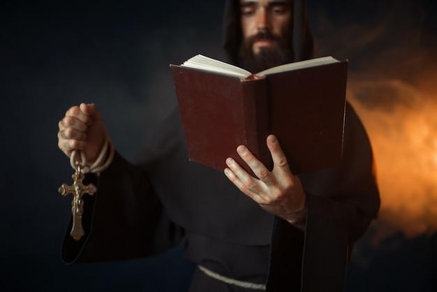 Średniowieczny mnich modlący się z książką w kościele