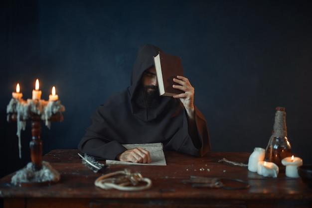 Średniowieczny mnich siedzi przy stole i czyta tajne pisma. tajemniczy zakonnik w ciemnej pelerynie. tajemnica i duchowość