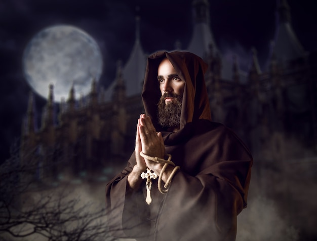 Średniowieczny mnich w czarnej szacie z kapturem modlący się nocą przed zamkiem i księżycem w pełni, sekretny rytuał. tajemniczy zakonnik w ciemnej pelerynie. tajemnica i duchowość