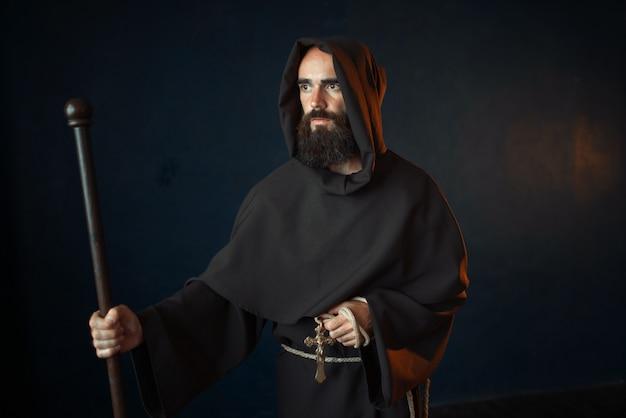 Średniowieczny mnich z drewnianym kijem i krzyżem w rękach