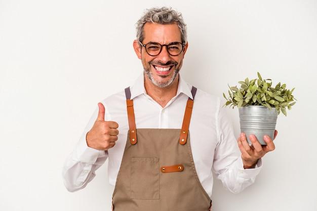 Średniowieczny ogrodnik kaukaski mężczyzna trzymający roślinę na białym tle uśmiechający się i unoszący kciuk w górę
