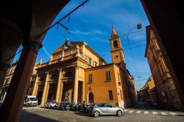 Średniowieczny portyk uliczny z kolorowymi domami na starym mieście w słoneczny dzień, bolonia, emilia-romagna, włochy