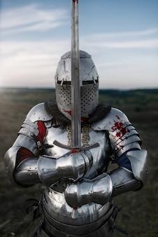 Średniowieczny rycerz w zbroi i hełmie pozach z mieczem, wielka bitwa. opancerzony starożytny wojownik w zbroi pozuje w polu