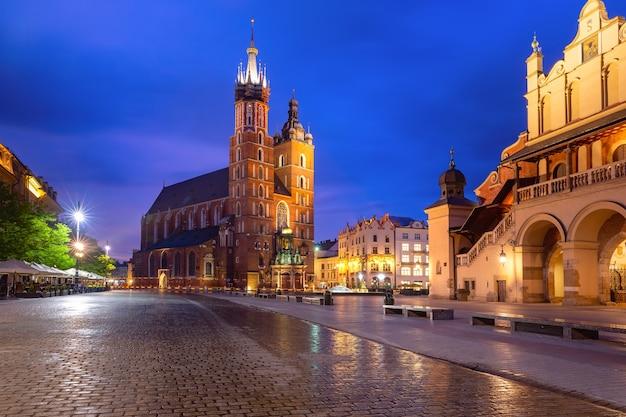 Średniowieczny rynek główny z bazyliką najświętszej marii panny na starym mieście w krakowie o wschodzie słońca