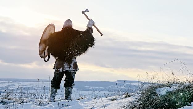 Średniowieczny wiking w zbroi krzyczy stojąc na zimowej łące o zachodzie słońca. rekonstrukcja średniowieczna.