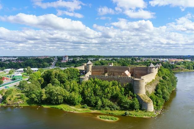 Średniowieczny zamek na pograniczu rosji i estonii nad rzeką.