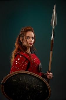 Średniowieczny żeński wojownik pozuje z włócznią, tarczą.