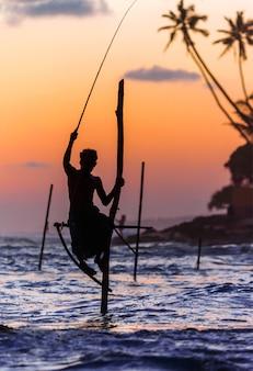 Sri lanka, słynni tradycyjni wędkarze z kijami o zachodzie słońca w welligama
