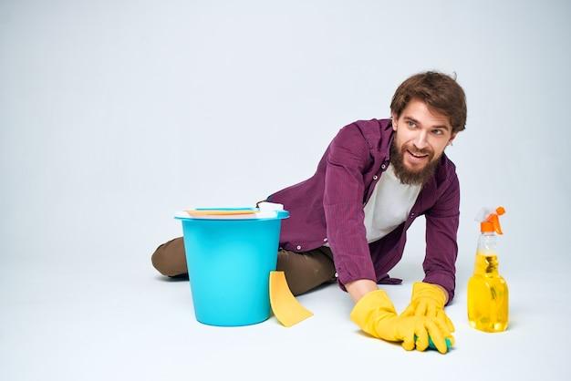 Środek czyszczący w rękawicach gumowych do mycia podłóg przy pracach domowych.