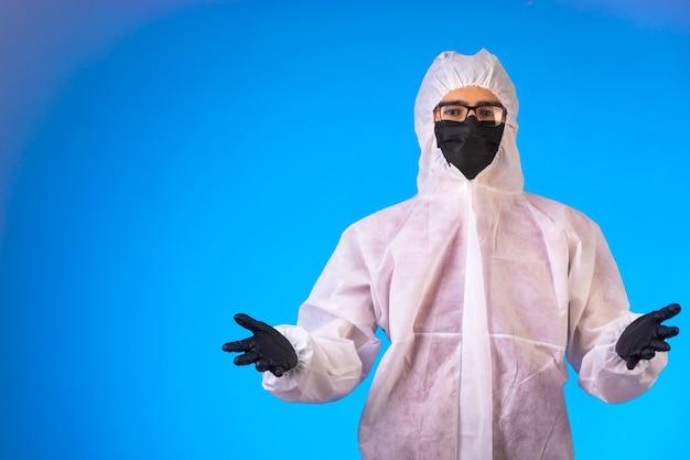 Środek dezynfekujący w specjalnym mundurze profilaktycznym otwiera ręce w wątpliwej pozycji.