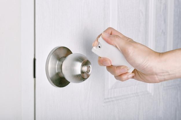 Środek dezynfekujący w sprayu alkoholowym, czyszczenie klamki drzwi zapobiegają rozprzestrzenianiu się zarazków koronawirusa, zdezynfekuj powierzchnię publiczną przed dotknięciem, covid-19 wybuch grypy pandemicznej przez ręczne dotknięcie.