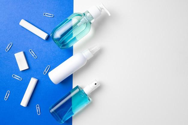 Środek do dezynfekcji rąk i przybory szkolne na papierze niebieskim i białym