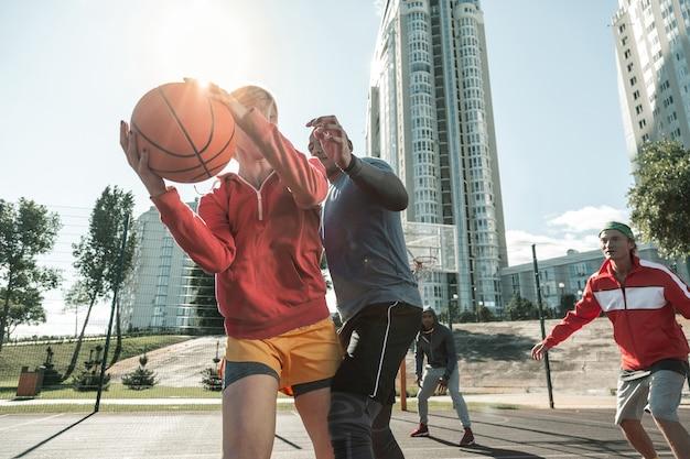 Środek gry. miły, silny mężczyzna, który próbuje przejąć piłkę, stojąc obok drugiego gracza