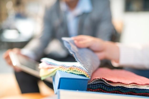 Środek męskiego projektanta przechodzącego przez próbki tkanin w studio.