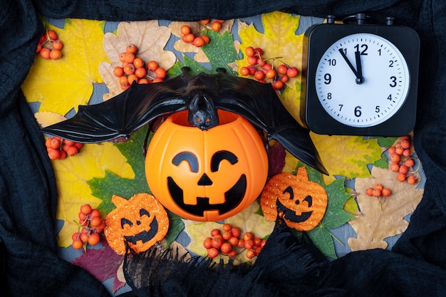 Środek nocy halloween. halloweenowa głowa dyni jack latarnia z czarnym nietoperzem i zegarem na tle kolorowych liści i czarnej ramce z szalika. czas świętować halloween