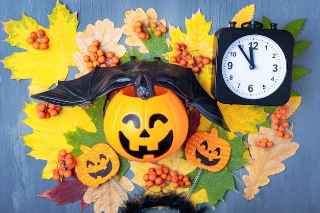 Środek nocy halloween. halloweenowa głowa dyni jack latarnia z czarnym nietoperzem i zegarem na tle kolorowych liści. szczęśliwa karta halloween. czas świętować halloween