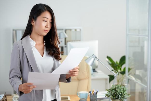 Środek strzelający azjatycka kobieta sprawdza biznesowych dokumenty