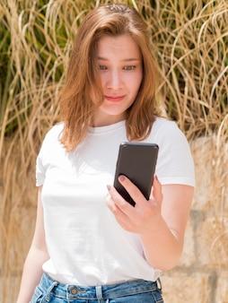 Środek strzelający dziewczyna patrzeje jej smartphone