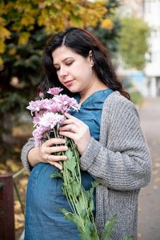 Środek strzelający kobieta w ciąży pozuje z kwiatami