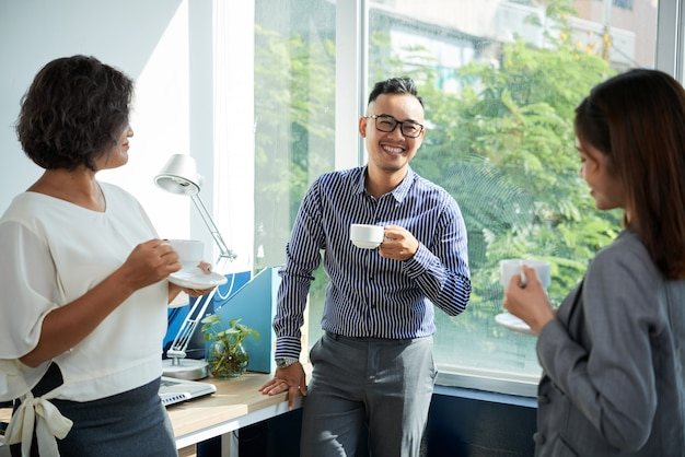 Środek strzelający ludzie biznesu cieszy się kawową przerwę przy biurowym okno