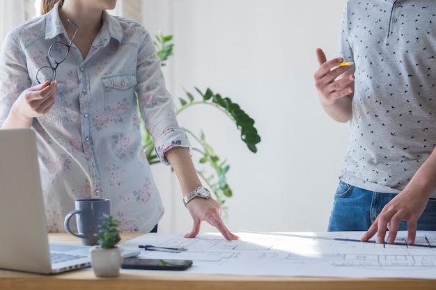 Środek współpracownika pracującego nad planem w biurze