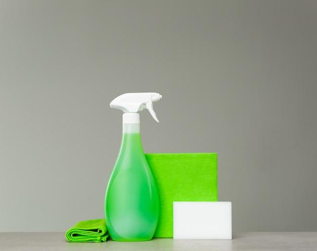 Środki czyszczące, zielona butelka z rozpylaczem z plastikowym dozownikiem, gąbka i ściereczka do kurzu