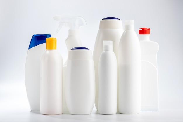 Środki do mycia włosów i ciała oraz środki do czyszczenia łazienki i okien. chemia gospodarcza na białej ścianie.