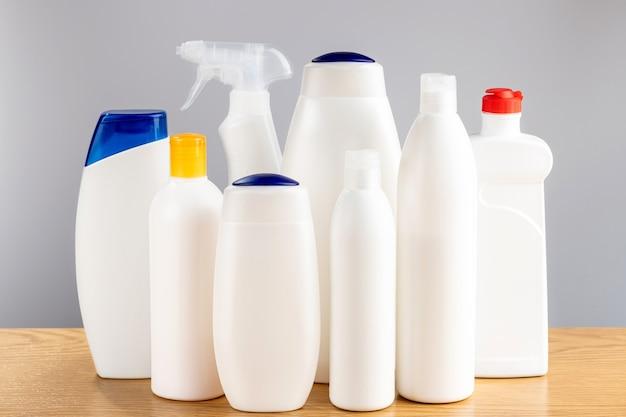Środki do mycia włosów i ciała oraz środki do czyszczenia łazienki i okien. chemia gospodarcza na szarej ścianie.