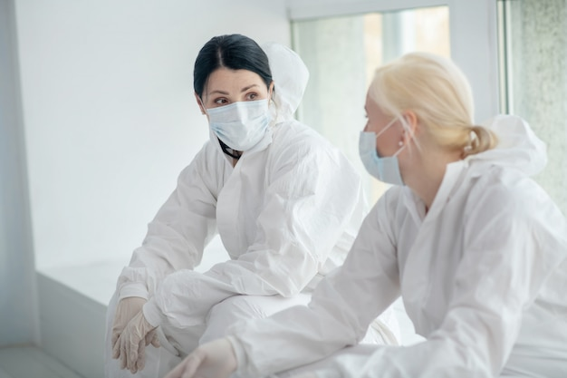 Środki ochronne. dwie pracownice medyczne w odzieży ochronnej i masce medycznej siedzą przy oknie i dyskutują o czymś