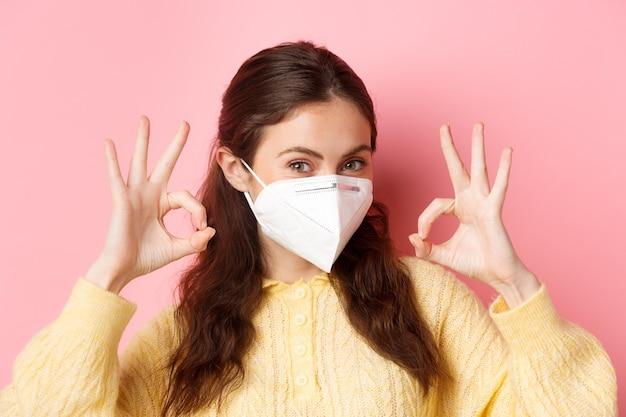 Środki zapobiegawcze, koncepcja opieki zdrowotnej. młoda glamour dziewczyna w respiratorze medycznym podczas pandemii covid-19, wykazująca dobre oznaki, chwaląca doskonały wybór, coś poleca.