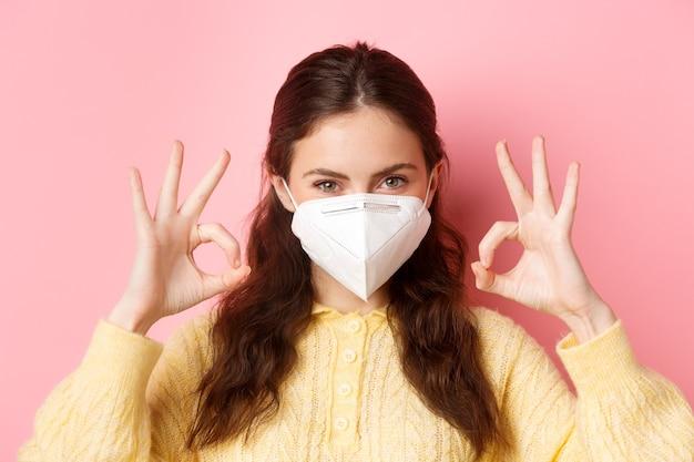 Środki zapobiegawcze, koncepcja opieki zdrowotnej. zbliżenie na pewną siebie atrakcyjną kobietę, noszącą respirator, wyglądająca na zdeterminowaną i pokazująca dobre oznaki, stojąca przed różową ścianą.