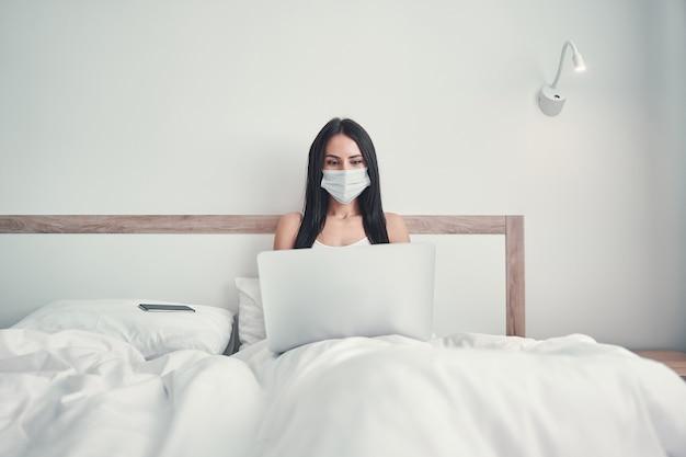 Środki zapobiegawcze. skoncentrowana długowłosa dziewczyna siedząca pod kocem i trzymająca komputer na kolanach
