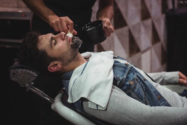 Środkowa część fryzjera nakładająca krem na brodę klientki
