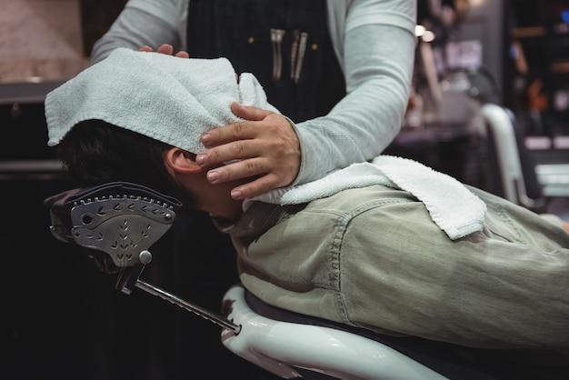 Środkowa część fryzjera wycierającego twarz klienta gorącym ręcznikiem