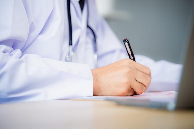 Środkowa część męskiego lekarza pisze receptę pacjentowi w worktable.prescribing treatment.