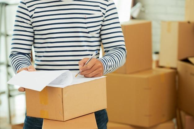Środkowa część mężczyzny w pasiastej koszuli z długim rękawem, wypełniająca formularz na pudełku
