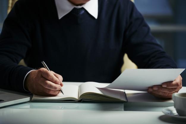 Środkowa część nierozpoznawalnego człowieka robiącego notatki