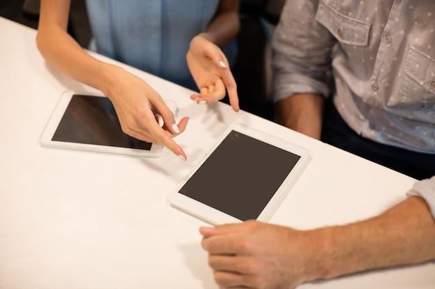 Środkowa sekcja współpracowników omawiających na cyfrowym tablecie