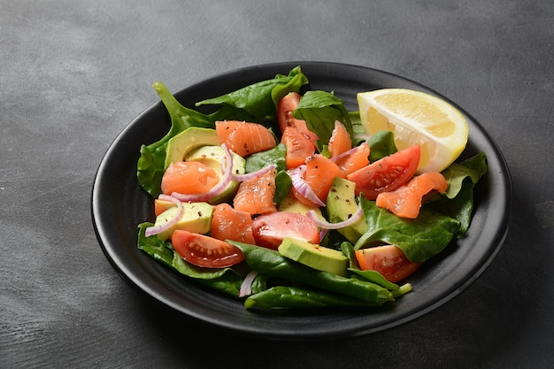 Śródziemnomorska sałatka z łososiem i awokado ze szpinakiem, pomidorkami koktajlowymi, awokado i dressingiem z czerwonej cebuli