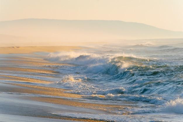 Śródziemnomorski koszt lub zachód słońca. tropikalny brzeg wyspy z silnymi burzowymi falami w ruchu. światło słoneczne na żółtym piasku za oceanem. rajski malowniczy pejzaż morski. piękna przyroda nadmorski krajobraz. zrelaksować się