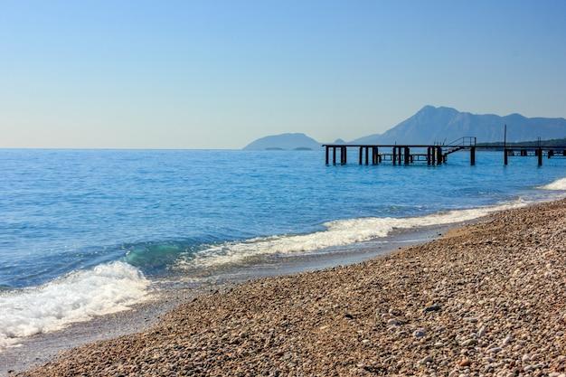 Śródziemnomorski krajobraz w antalya, turcja. błękitne morze, molo i góry.