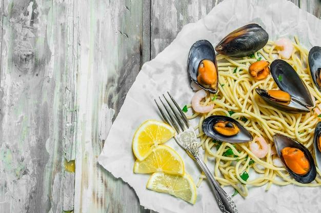 Śródziemnomorski makaron. owoce morza spaghetti z małżami na papierze. na rustykalnym tle.