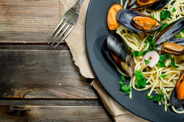Śródziemnomorski makaron. spaghetti z owocami morza z małżami i limonką. na drewnianym.