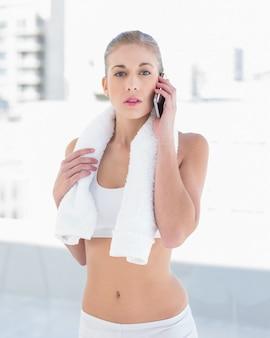 Srogo młody blondynka model dzwoni z jej telefonem komórkowym