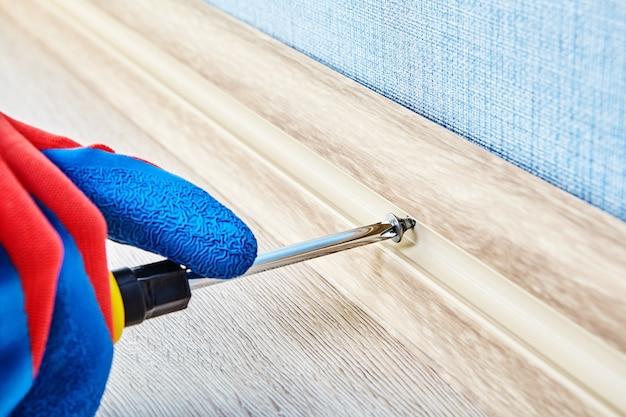 Śruba mocująca w elastycznym cokole do podłogi za pomocą narzędzia ręcznego przez elektryka.
