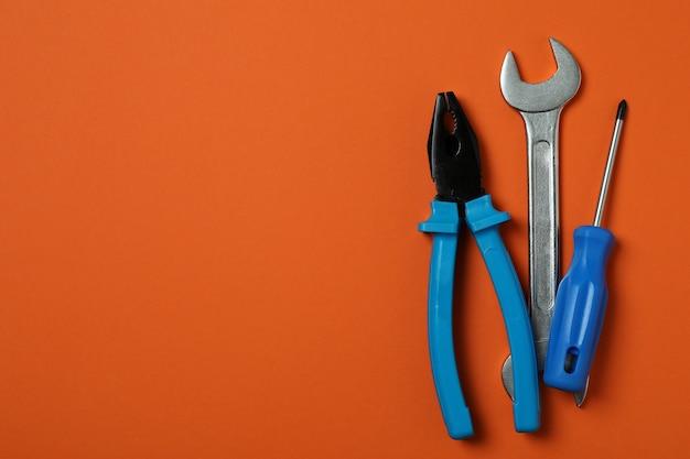 Śrubokręt, klucz i szczypce na pomarańczowo